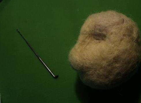 Начинаем делать голову обезьяны. Для этого бесцветную шерсть скатывайте в плотный шарик. Притупите к валянию.