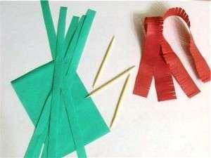 Возьмите бумагу для квиллинга красного и зелёного цвета. Нарежьте её на широкие и узкие полоски. На красных полосках нужно сделать надрезы.