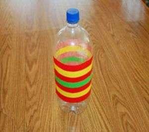После этого возьмите цветную изоленту и обклейте ей по кругу прямую часть бутылки. Если использовать разные цвета, то поделка получится весьма оригинальной.