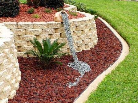 Сначала рассыпьте декоративный гравий по выровненной поверхности земли и оформите края мнимого водоема растительностью