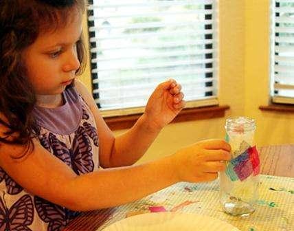 Одной из самых простых поделок ко дню учителя можно назвать вазу. Для её оформления вам понадобится обычная банка, цветная бумага тишью, клей ПВА и ножницы. Пусть ребёнок разрежет бумагу на одинаковые квадраты, можно попробовать вырезать фигурки и другой формы. Затем смажьте поверхность банки ПВА и приклеивайте к ней постепенно квадратики. Осталось дождаться полного высыхания и ваза для учителя готова.