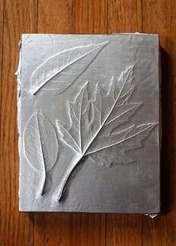 Теперь клеем намажьте снова листья и приложите фольгу. Заранее отрежьте большой кусок фольги, чтобы ее хватило на всю основу. Красиво задекорируйте фольгу, чтобы она плотно прилегала к деревянной основе.