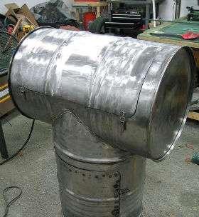 В большой бочке топка размещается под коптильней для мяса. Камера для топки делается из кирпича. В кирпичной кладке делается проём для опилок и входа воздуха. Резервуарная ёмкость ставится на кладку.